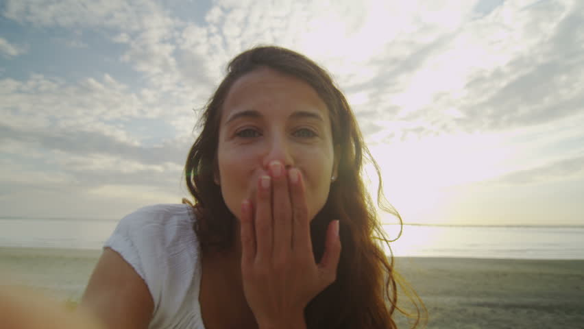 4K Attractive young woman takes a video call on the beach near sunset, shot on RED EPIC | Shutterstock HD Video #10008386