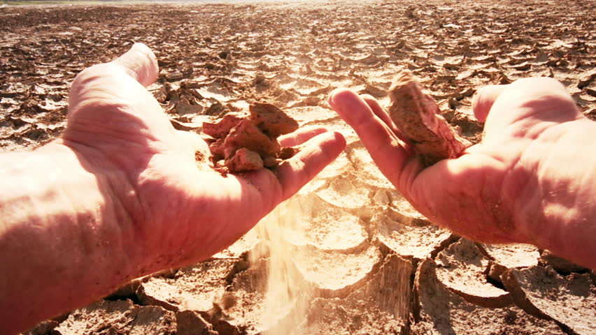 Farmer's hands split piece of dry soil from field affected by drought. Slow motion video of deserted cracked barren soil