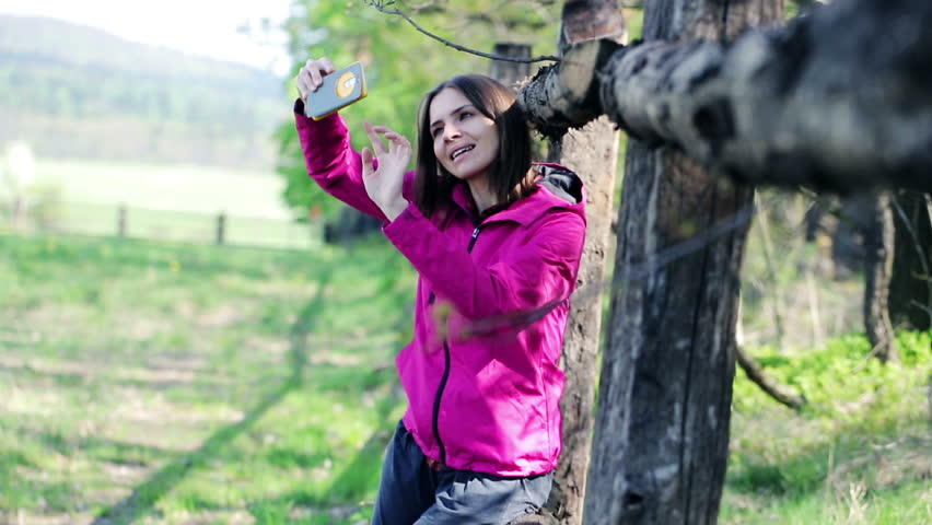 Young, pretty woman taking selfie photo on the country fence 