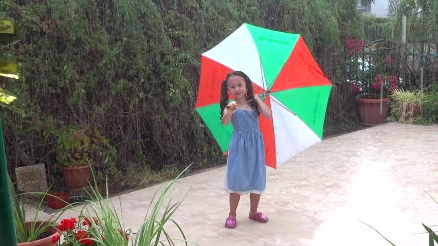 JERUSALEM, ISRAEL - SEPTEMBER 8 2014: girl dancing in rain with umbrella - HD stock footage clip