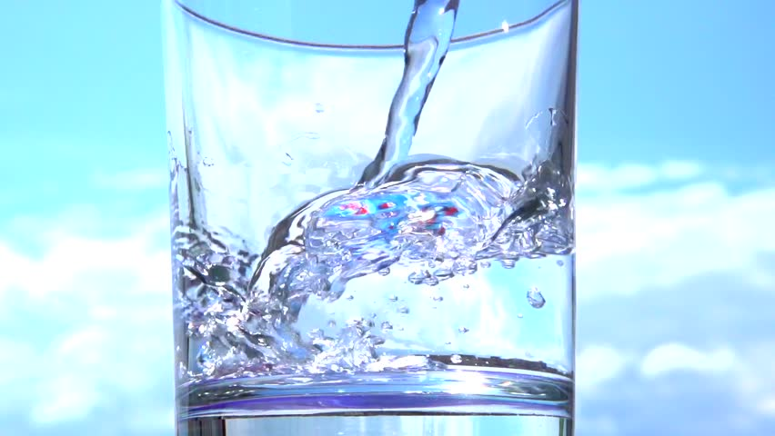 Clean water is poured into a glass on a background of blue sky. Slow motion 240 fps. High speed camera shot. Full HD 1080p.  - HD stock video clip