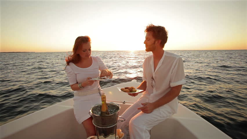 young couple in white sitting on boat at sunset with champagne and appetizer