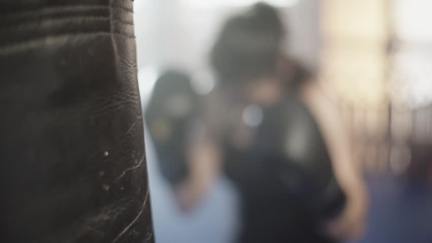 Close up of a boxing glove hitting a punching bag. Female boxer at slow motion. | Shutterstock HD Video #10128887