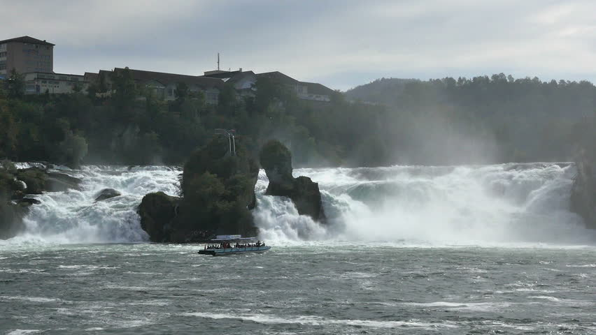 RHINE FALLS, SWITZERLAND - SEPT. 2014: Tour-boat takes tourists close to Rhine Falls  near the town of Schaffhausen,Switzerland. Tour-boats take tourists up to the mists below the falls.  - HD stock footage clip