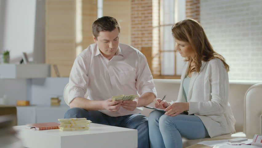 Husband counting money, telling wife good news, rich family | Shutterstock HD Video #10197251