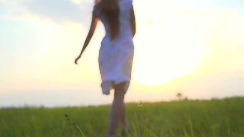 Beautiful Girl in white dress enjoying nature on a spring field. Beauty young woman dancing, spinning and laughing outdoors. Health care concept. Raising hands. over sunset sky. Slow motion, 1080p - HD stock video clip