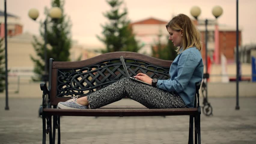 General-up shot woman editor in chief looks album photographer portfolio, sitting on a bench in downtown de-focused background of trees, lights and buildings | Shutterstock HD Video #10223540