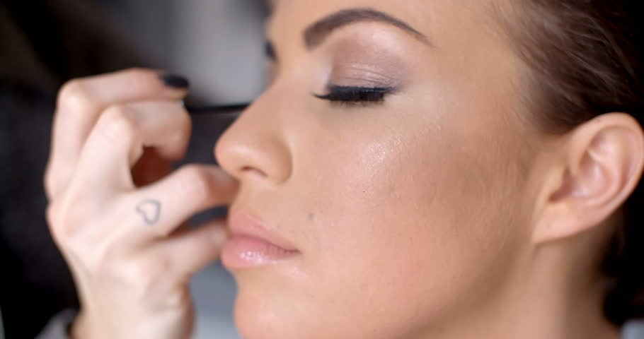 Pretty dark haired woman applying eye liner on her eyelid with a thin applicator in a beauty concept - 4K stock footage clip
