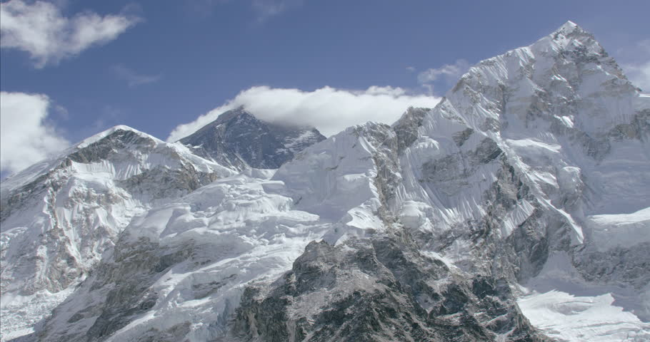 Massive rocky mountain summit peak sharp jagged cliff edge wide shot aerial POV of snowcapped ice himalayan mountains in Nepal Tibet China | Shutterstock HD Video #10239974