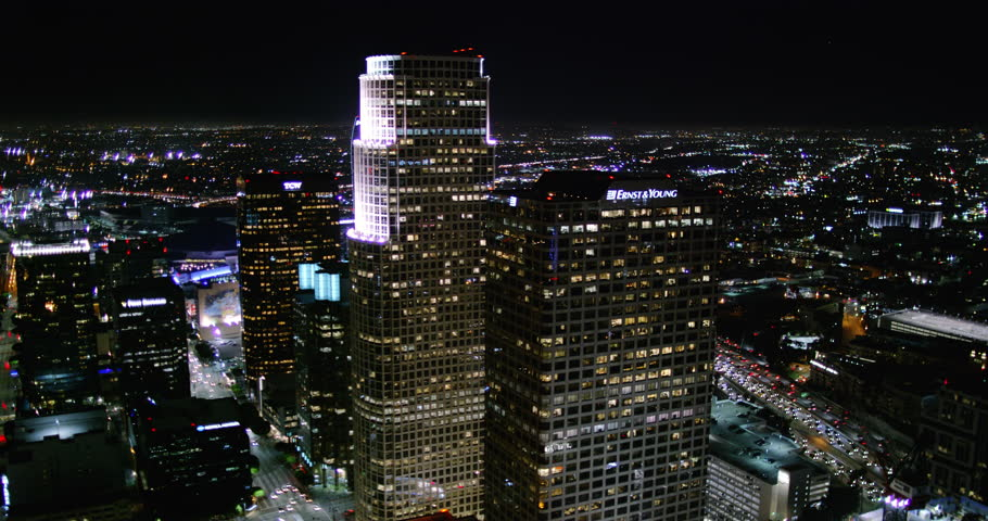Sexy aerial wide shot of downtown Los Angeles skyscrapers at night showing city lights and building towers from a helicopter point of view with urban streets and traffic.