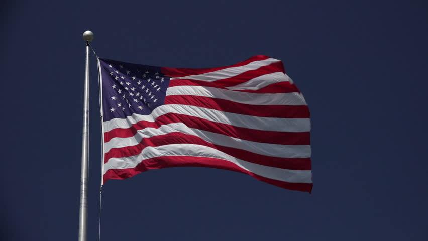 Looking up at high flying jumbo American flag waving in the breeze against a beautiful blue sky on a sunny day - 4K stock video clip