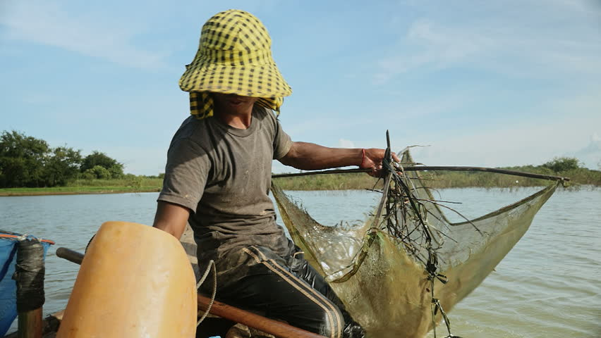 Close up of prawn fisherman baiting net, dropping it deeper into a river and rowing boat for a new catch