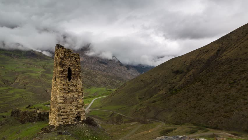 Time lapse. Russia, the Caucasus Mountains, North Ossetia,  the formation of clouds in the ancient settlement with a thousand year history - Fiagdon. Security tower - HD stock video clip