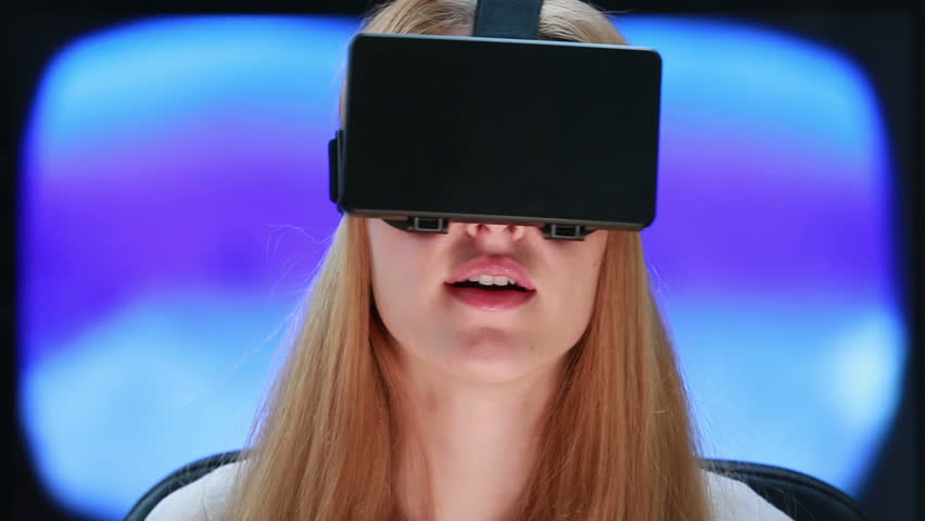 Virtual reality game. Girl with pleasure uses head-mounted display. | Shutterstock HD Video #10289456