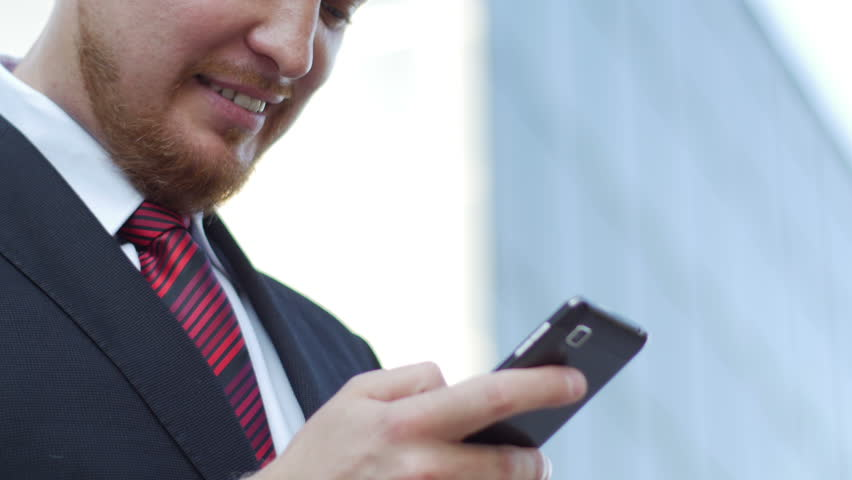 Adult, attractive businessman standing near office building uses a smart phone. He is dressed in an expensive suit with a red tie and looks very successful and happy. Filmed in 4K resolution | Shutterstock HD Video #10300382