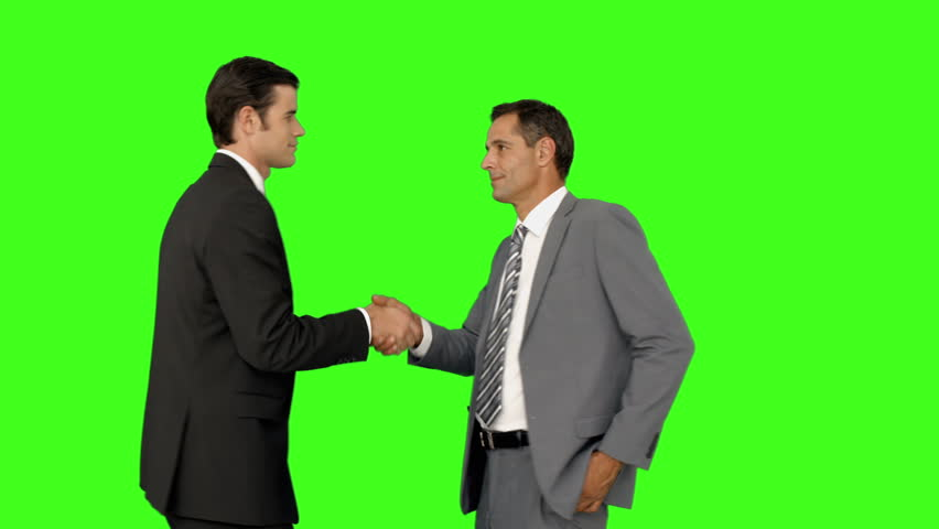 Businessmen shaking hands and smiling on green screen background - HD stock footage clip