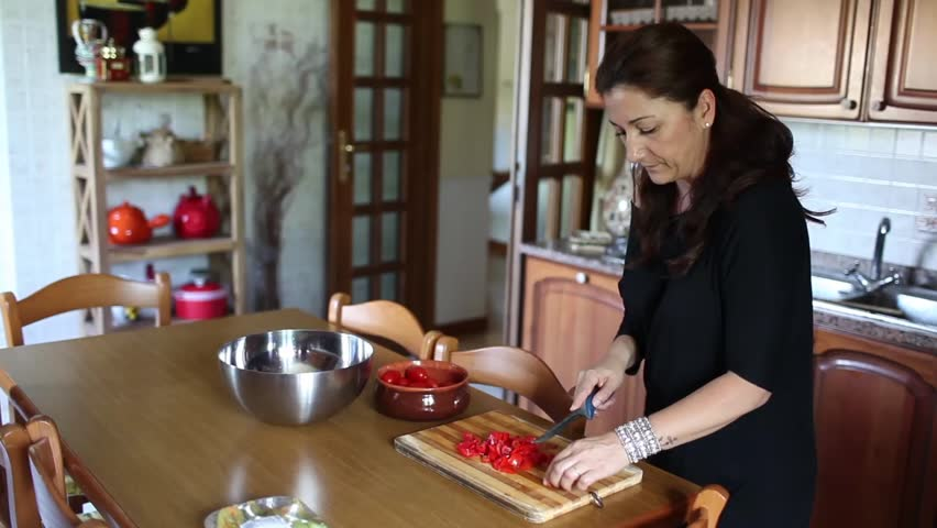 Video clip of housewife in the kitchen, cutting tomatoes on the table.