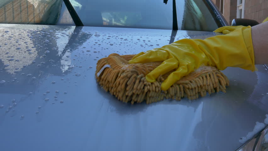 Woman's hand in yellow gloves washing a car | Shutterstock HD Video #10327859