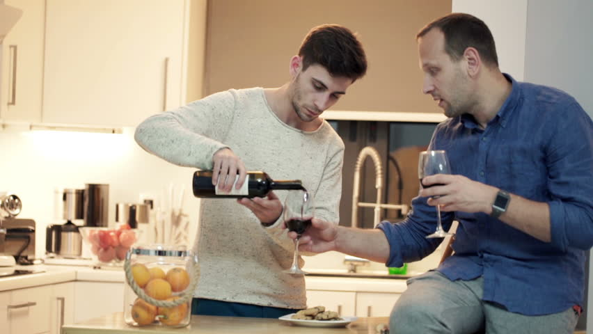 Young, handsome friends talking and drinking wine in the kitchen at home  - HD stock footage clip