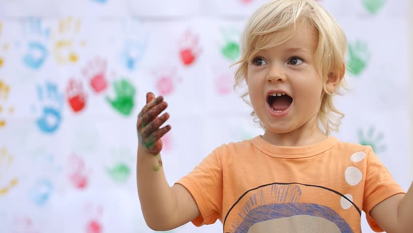 Amazing cute happy child surprising, saying wow and rubbing color paint on his little hands on color handprints background 50fps""
