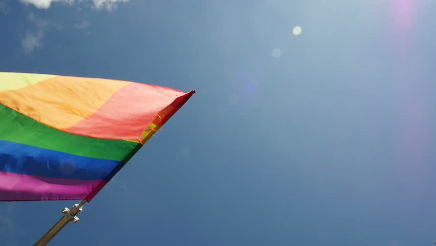 Slow motion of rainbow flag waving against blue sky. Commonly the gay pride flag and sometimes the LGBT pride flag, is a symbol of lesbian, gay, bisexual, and transgender LGBT pride and LGBT movements | Shutterstock HD Video #10362257