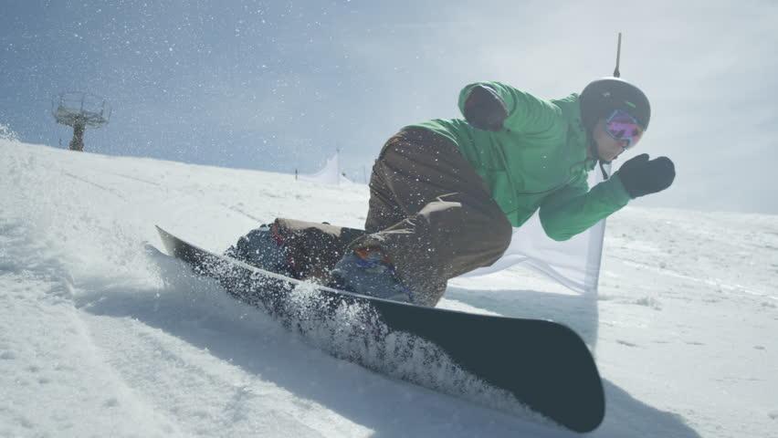 Slow motion close up racing snowboarder riding slalom