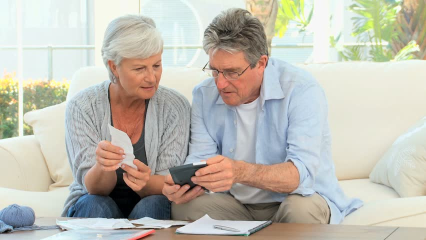 Elderly couple calculating their bills in the living room - HD stock footage clip