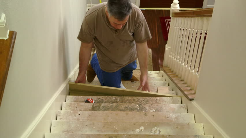 A tradesman or handyman homeowner type fitting in stair riser and measuring for the tread portion of the step. - HD stock footage clip
