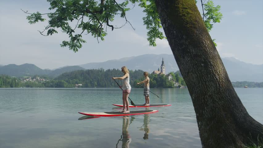 SLOW MOTION: Young couple stand up paddling on lake Bled on beautiful sunny day - HD stock footage clip