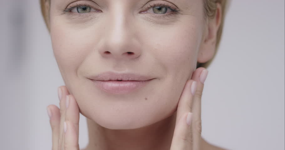 Close up of Beautiful healthy woman touching smooth skin on face in slow motion for beauty skincare concept on a grey background Shot in 6K on RED EPIC DRAGON - 4K stock footage clip