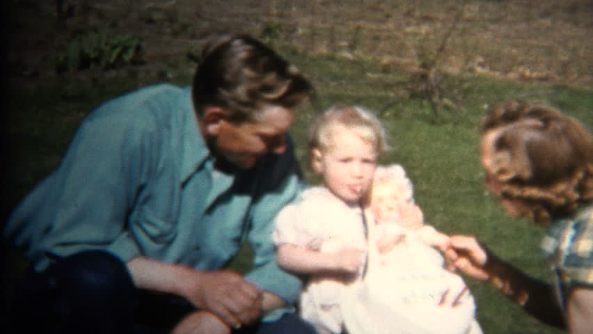 IOWA, USA - JULY 1952: Dad Mom & Baby at Farm Picnic where chickens roam just behind the fence.