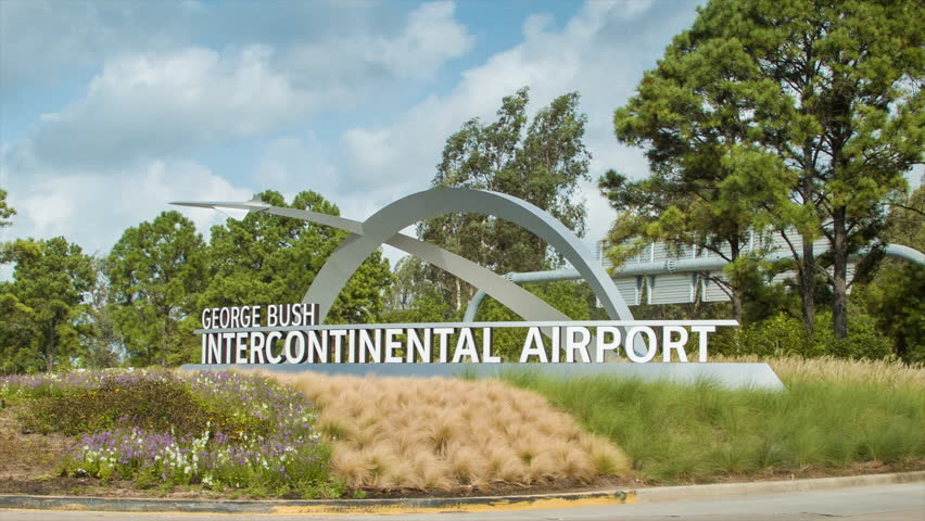 HOUSTON, TX - 2015: Cars Driving Into Houston George Bush Intercontinental IAH Airport on a Nice Day panning from the Welcome Sign to the Entering Vehicles