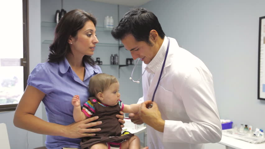 Handsome Pediatrician Holding Baby Boy In His Office At