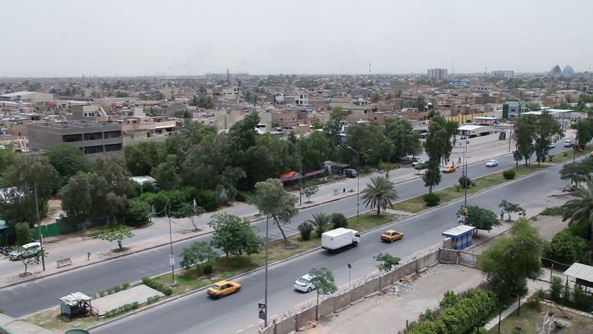 Car traffic on Palestine Street with Baghdad skyline, Iraq, pan right
