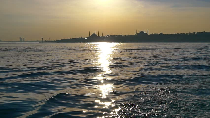 Glittering sea of Bosphorus just in time for sunset. Slow Motion. Hagia Sophia and Blue Mosque in the distance. Istanbul, Turkey. SM