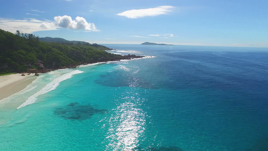4k beach footage, flying over different blue colored ocean, sandy beach, granite rocks of tropical island