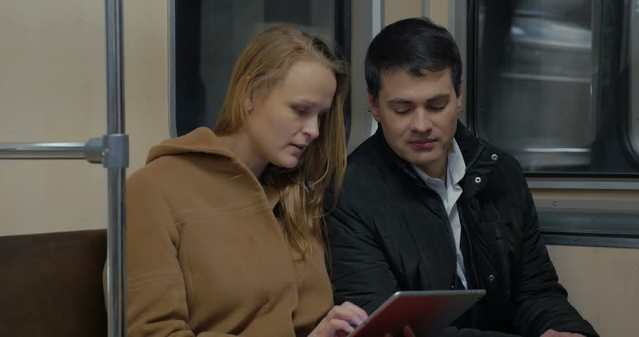 Young man and woman in moving underground train. They using pad and talking during the ride - 4K stock footage clip