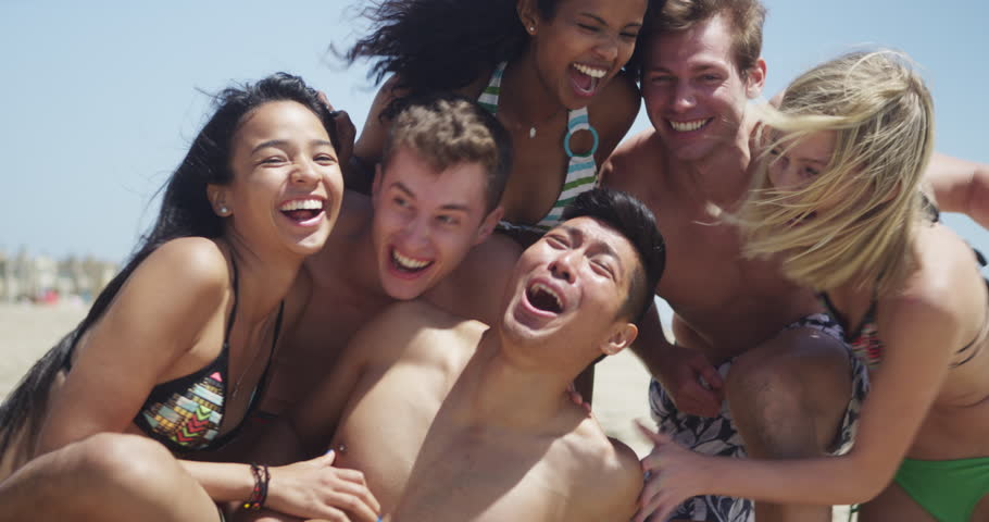 Healthy young group of multi ethnic friends smiling at camera on the beach