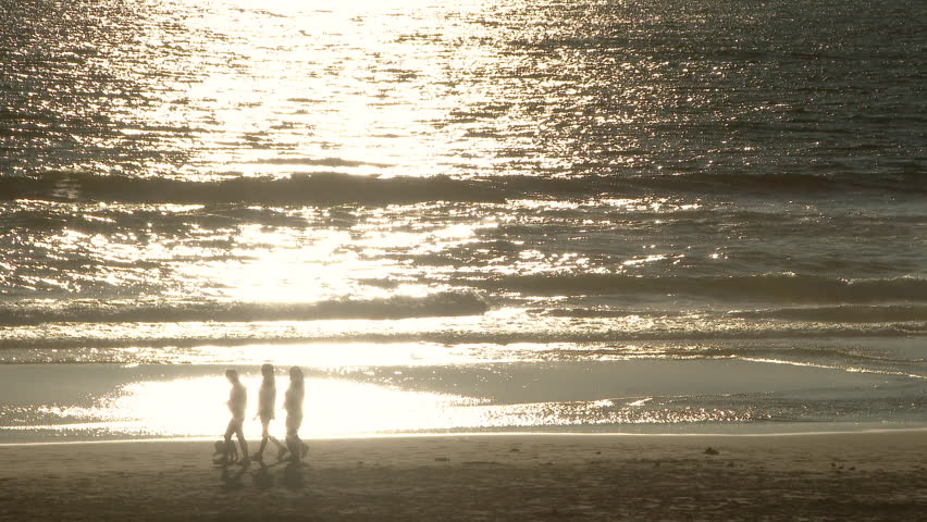 Three unrecognizable girls walking along Pacific Ocean coast at sunset with their dog.