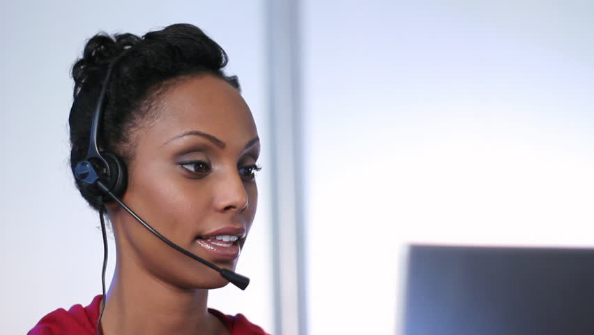 Call center. Young woman with headset talks to a customer while looking at her computer monitor.