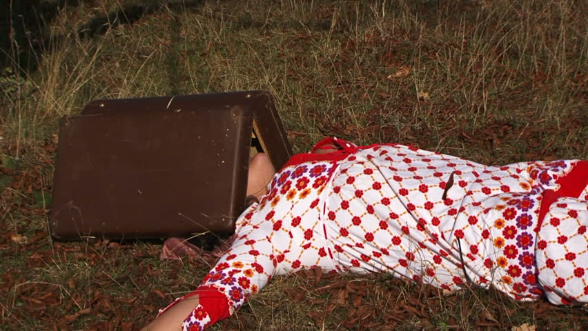 This is a video shot of a weird plus sized  woman in white and red dotted gown lying on the gray faded grass in the meadow with opened suitcase on her head clapping on it with her hands. Side view. - HD stock footage clip