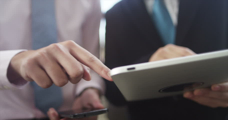 4K Close up on the hands of 2 businessmen using mobile technology outdoors | Shutterstock HD Video #10623158