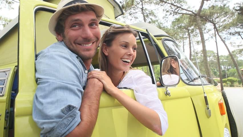 Couple standing by vintage camper van window | Shutterstock HD Video #10625363