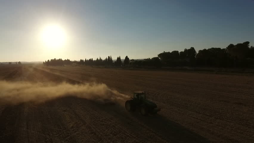 AERIAL: Tractor plowing field at sunset.