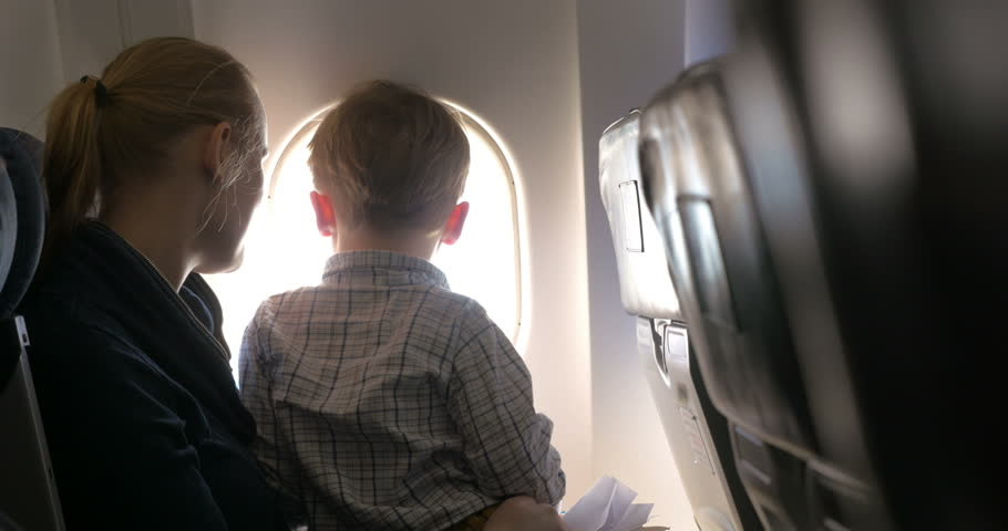 Son sitting on mothers lap in plane and they enjoying view from illuminator, mom kissing the boy and telling something to him