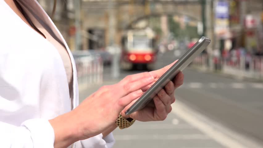 young attractive blonde woman works on tablet - urban street with tram in the city - closeup