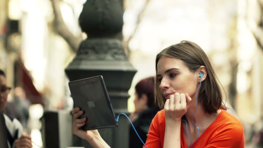 Young woman watching movie on tablet computer sitting in cafe in city  | Shutterstock HD Video #10646918