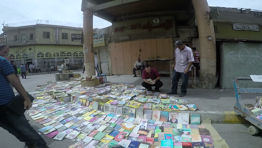 BAGHDAD, IRAQ - MAY 2015: Men look for books at Mutanabbi Street in Baghdad. Mutanabbi Street where writers and intellectuals meet is the historic center of Baghdad bookselling