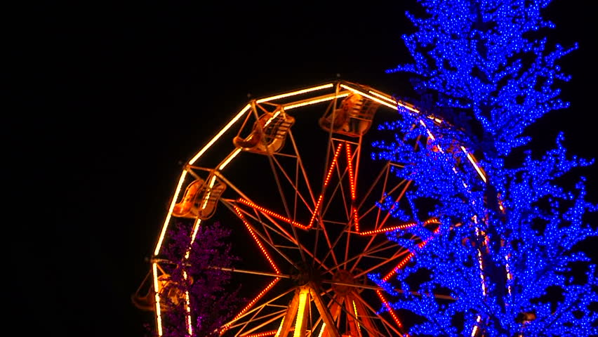 This shot was captured at night -  ferris wheel decorated with bright yellow and orange lights spinning around at night. Trees decorated with blue and purple lights are by sides.    Shutterstock HD Video #10685897