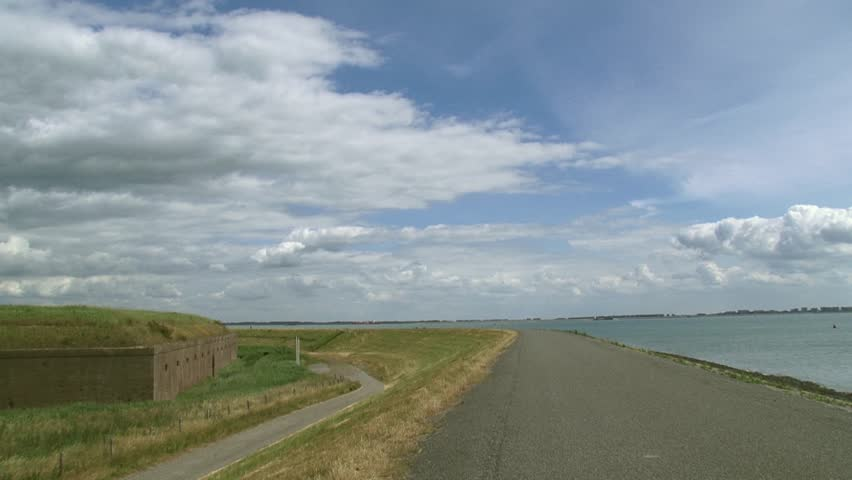 ZEELAND, THE NETHERLANDS - JUNE 2015: Sea dike + pan Fort Ellewoutsdijk, a coastal fort anno 1835 along the Western Scheldt to control the ships and guarantee a safe passage to the Port of Antwerp  | Shutterstock HD Video #10687976